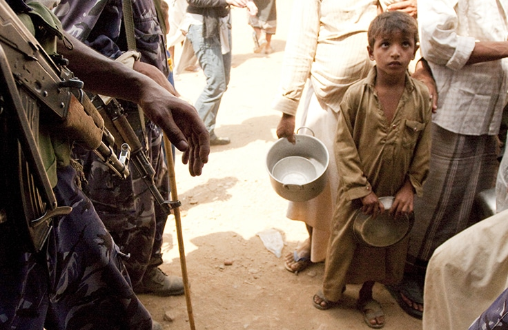 A young boy at Northern Yemen, Mazraq refugee camp waits in line for food